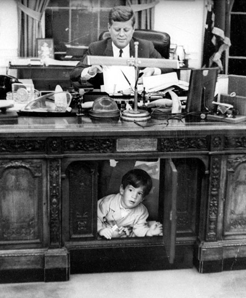 John F. Kennedy Jr. playing under John F. Kennedy's desk.