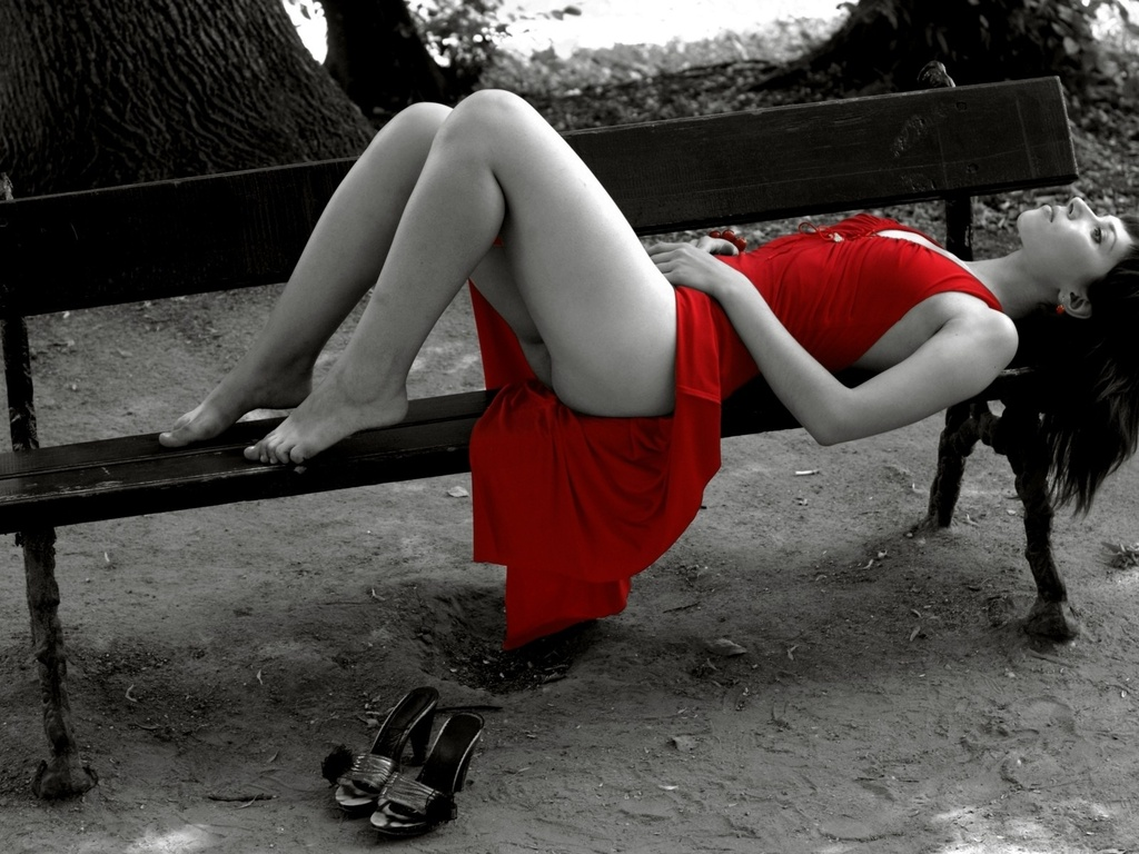 Woman wearing a red dress, lying on bench.