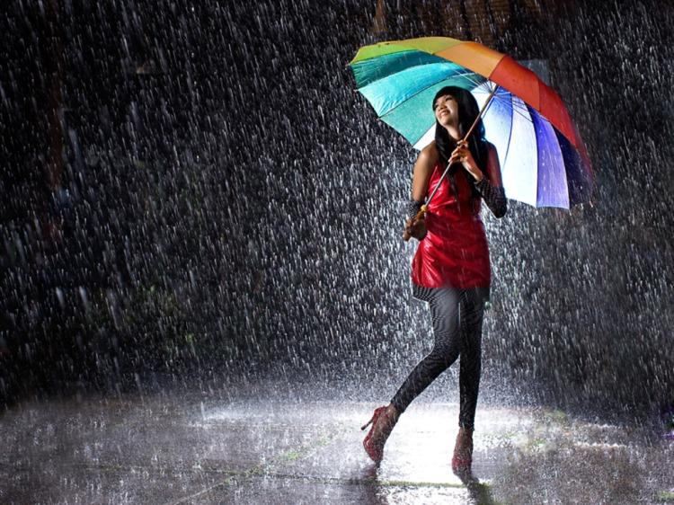 Girl under a colored umbrella.