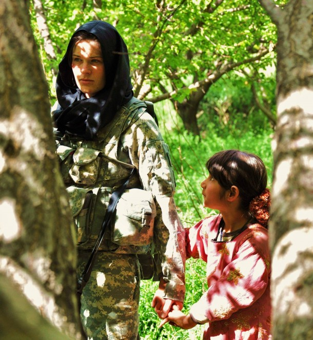 Young Afghan girl holds hands with a female American Soldier.