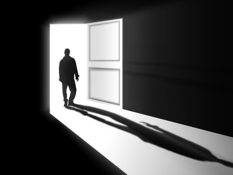 Black and white figure standing in doorway.