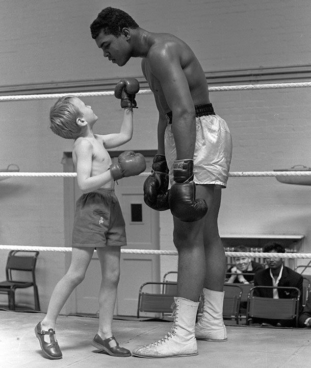 Muhammad Ali with 6 years old Patrick Power in the ring during his training for the heavyweight title fight against Harry Cooper, 1963.