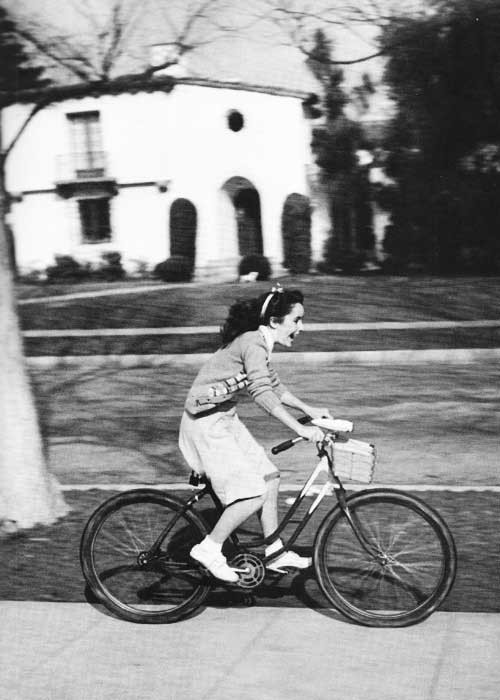 A 12 year old Elizabeth Taylor riding her bike through Beverly Hills, 1944.